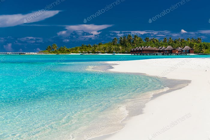 Over water villas in Maldives and a white beach with palm trees