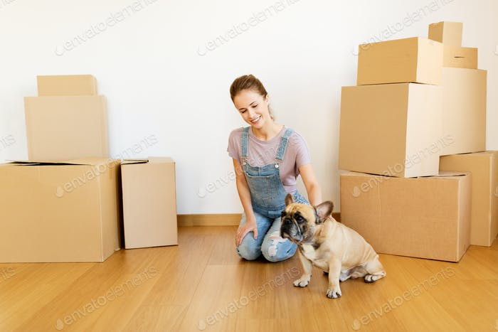happy woman with dog and boxes moving to new home