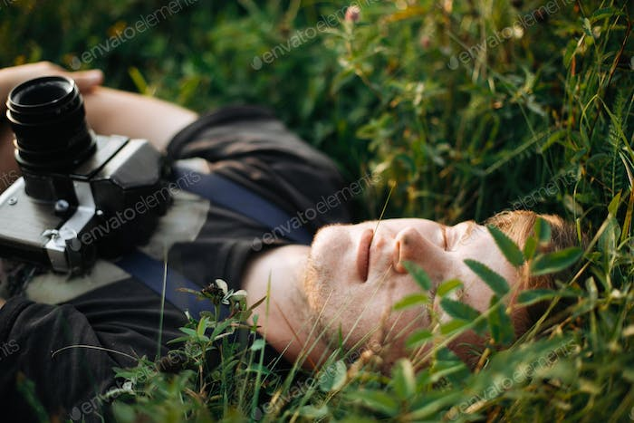 Handsome guy resting in nature and enjoying evening in mountains