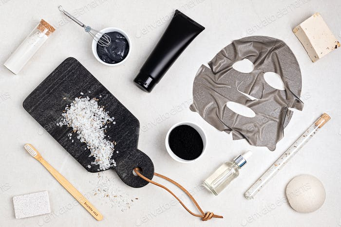 Flat lay of cosmetic products on the basis of activated charcoal, top view. Beauty and natural skin