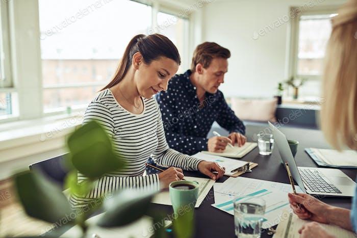Lächelnde Geschäftsleute mit einem Treffen um einen Bürotisch