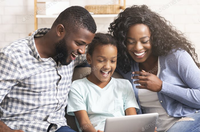 Black family watching funny videos on digital tablet at home