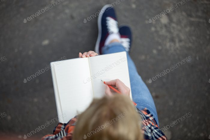 Student girl writing with a pencil in a notebook