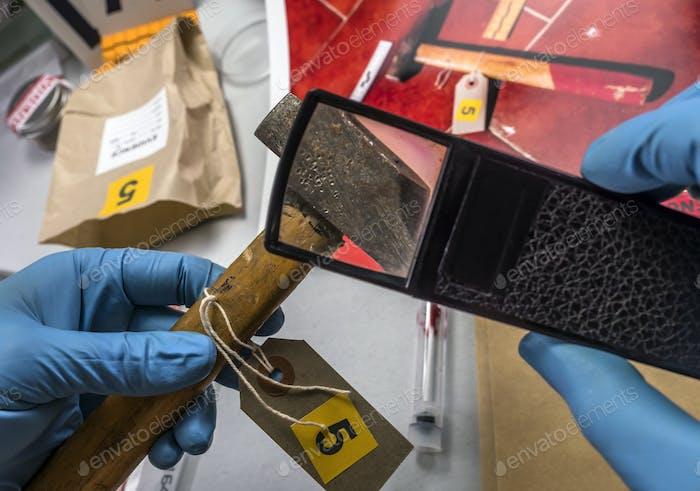 Experte Polizei untersucht mit Lupe einen Hammer