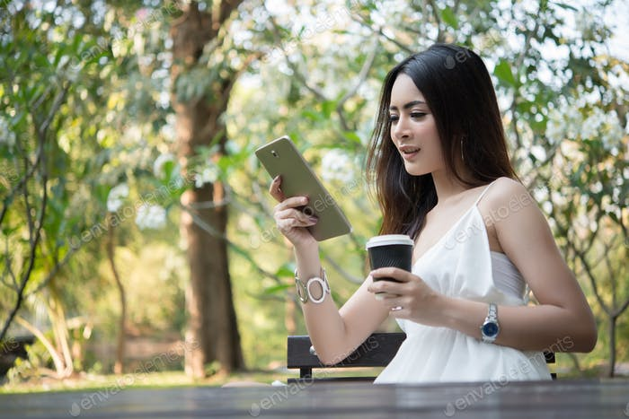 Young beautiful woman holding disposable coffee cup while text messaging through smartphone.