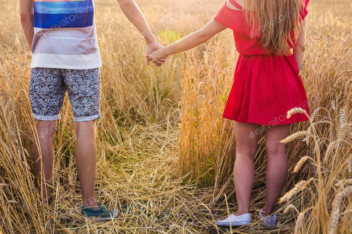 Back view of beautiful love couple holding hands outdoors over a summer field background