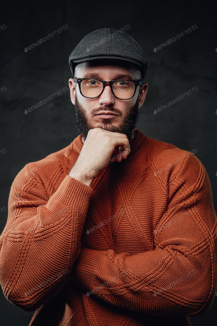 Brutal and stylish hipster poses with hand under his chin in studio