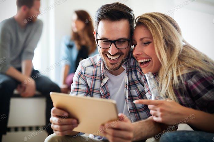 Fröhliches Paar mit digitalem Tablet entspannen zu Hause