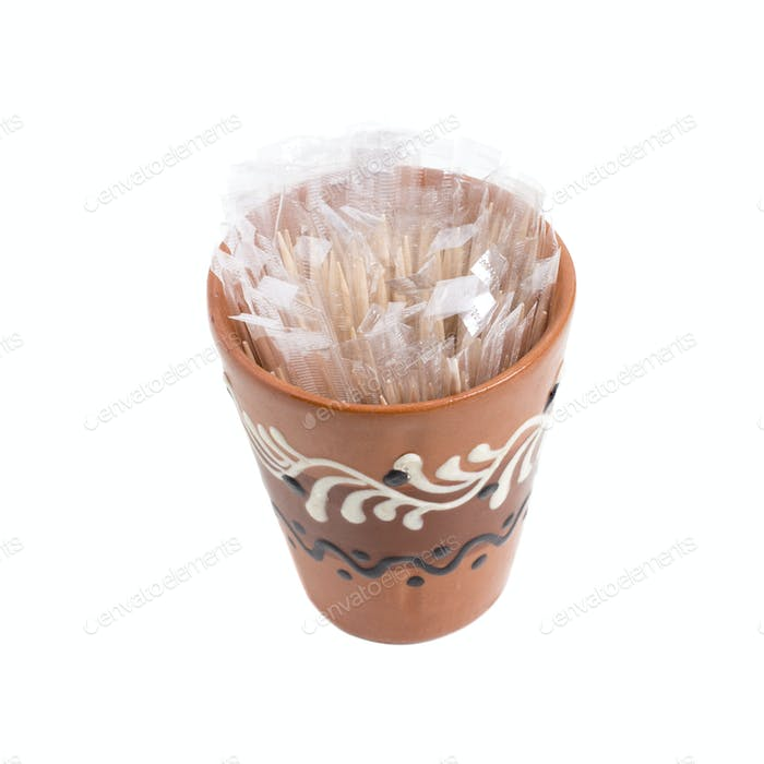 Clay cup with toothpicks.