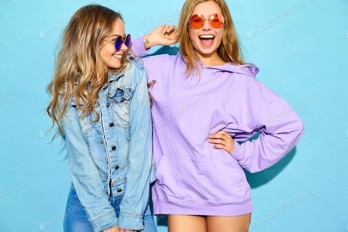 Portrait of two cute young woman posing in studio