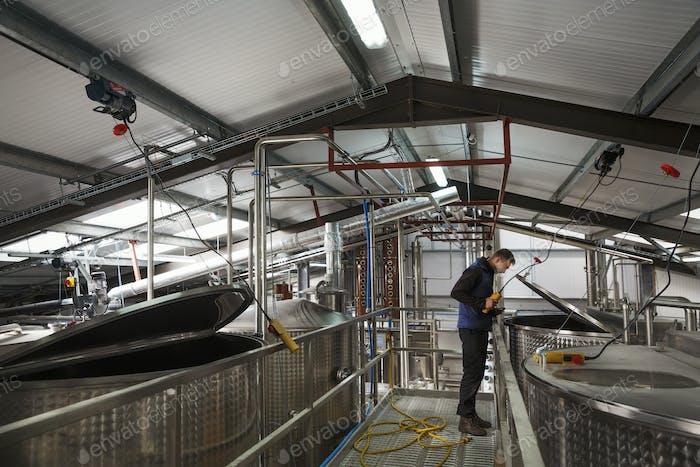 Man überprüft große Metalltanks in einer Brennerei oder Brauerei, hebt den Deckel auf einer Kammer voller Bier
