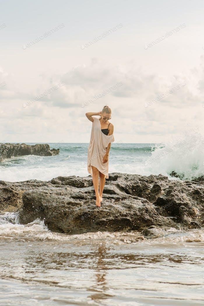 Una Mujer bonita cerca de las rocas de peligro en la orilla del océano.