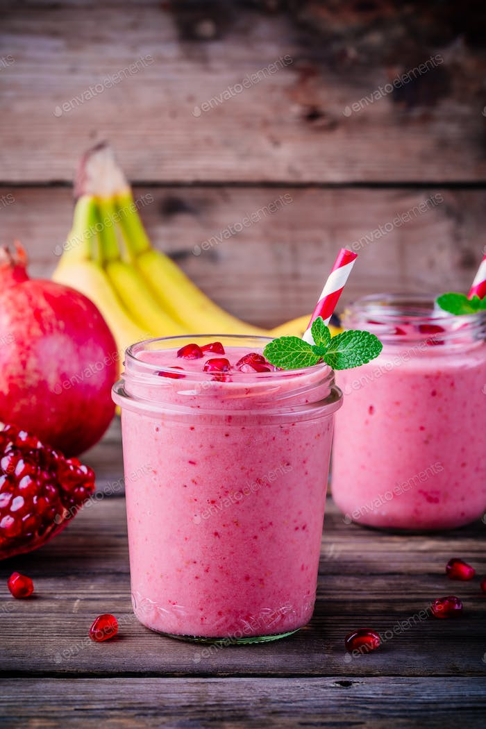 Pink pomegranate smoothie in a glass jar with mint and fresh seeds