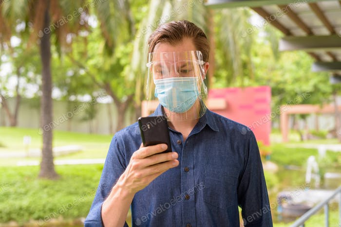 Face of young man using phone with mask and face shield for protection from corona virus outbreak at