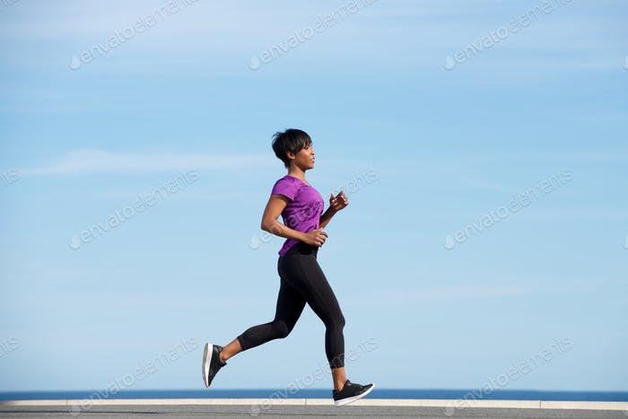 Full body side fit young african woman running outdoors against blue sky