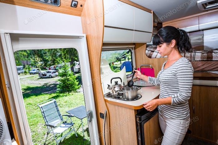 Woman cooking in camper, motorhome interior