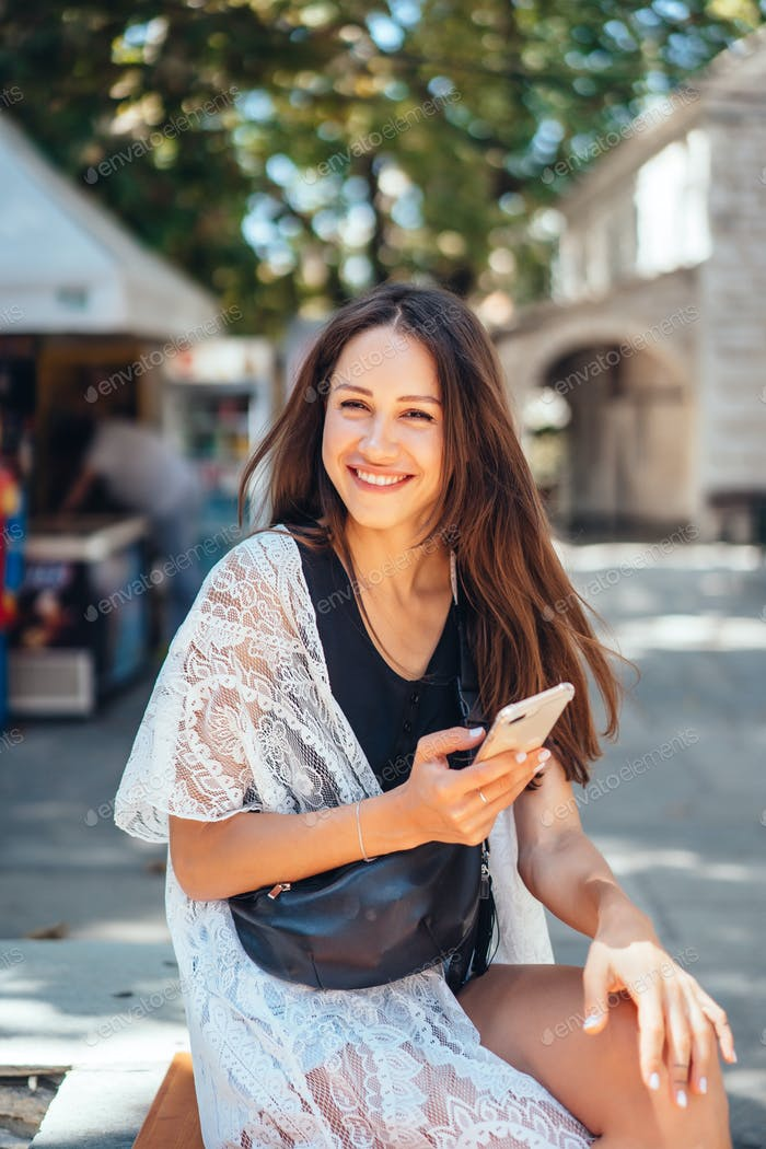 A girl is holding a phone and posing on the camera. The Internet. Message