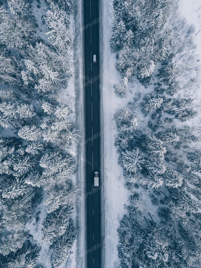 Carretera de campo que pasa por los hermosos paisajes cubiertos de Nieve. Aéreo.