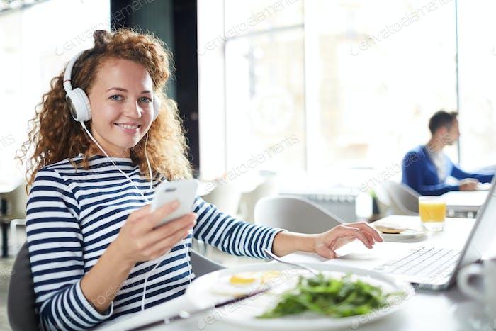 Happy girl choosing track on smartphone