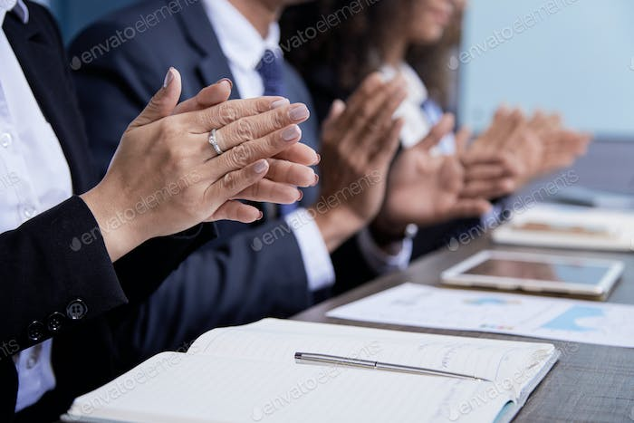 Crop colleagues clapping on meeting