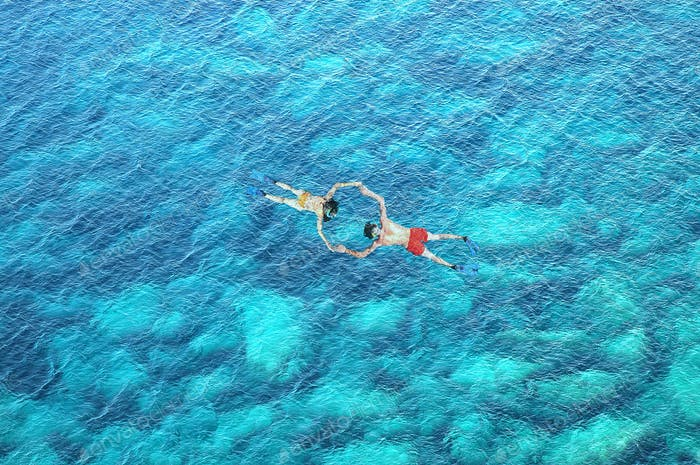 Drone view of couple snorkeling in clear blue sea water