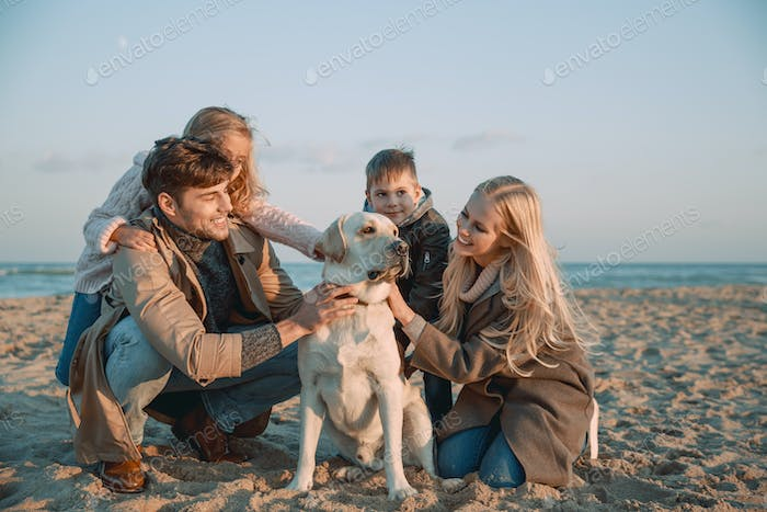 happy family with labrador dog at seaside