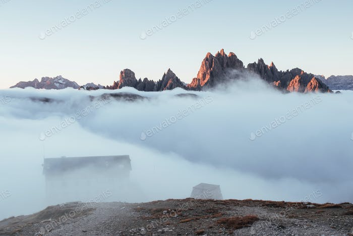 The buildings is in dreamy white mist with dolomite mountains on background