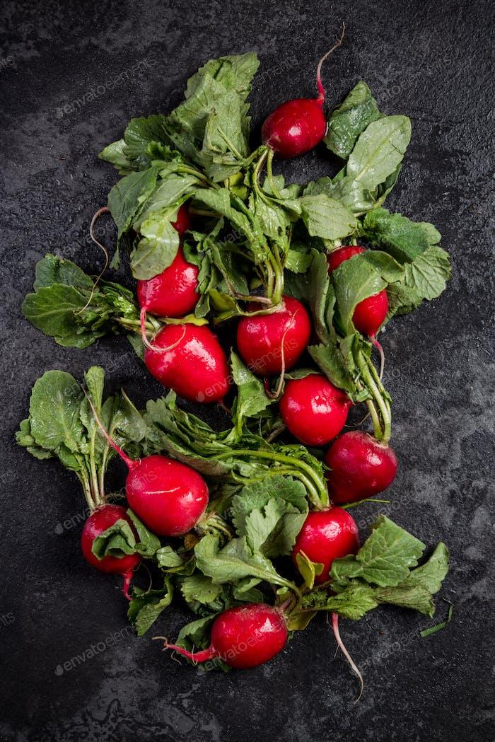 Market fresh organic radish with leaves on dark background