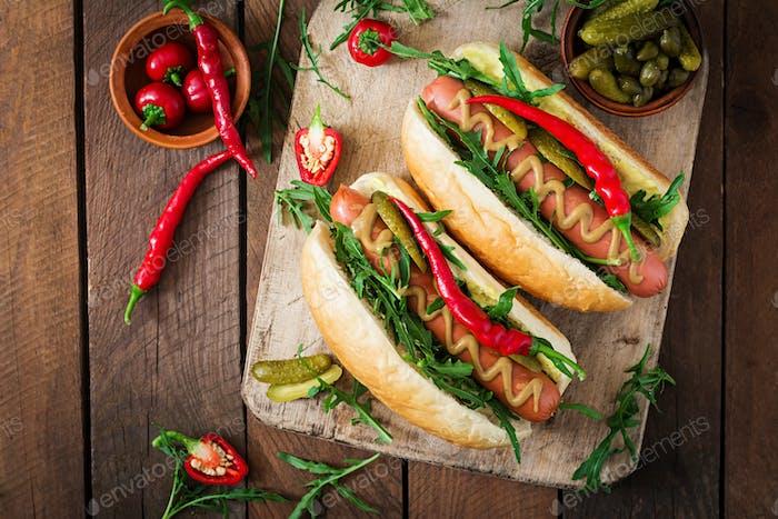 Hot Dog mit Gurken, Kapern und Rucola auf hölzernem Hintergrund. Ansicht von oben