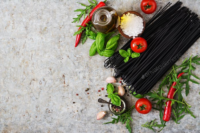 Ingredients for black linguine pasta - tomato, basil, chili . Top view