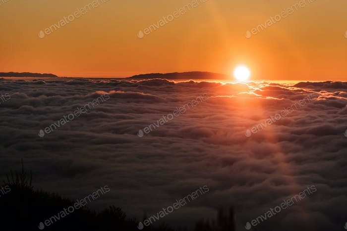 a spectacular sunset above the clouds in the national Park of the volcano Teide on Tenerife