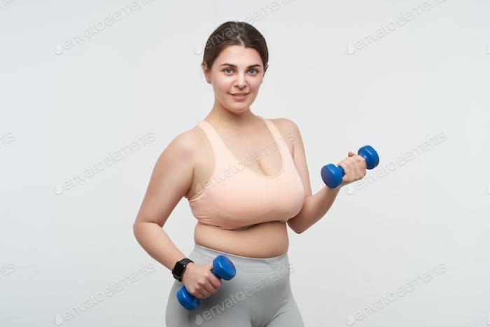 Studio photo of young positive oversized female exercising with dumbbells