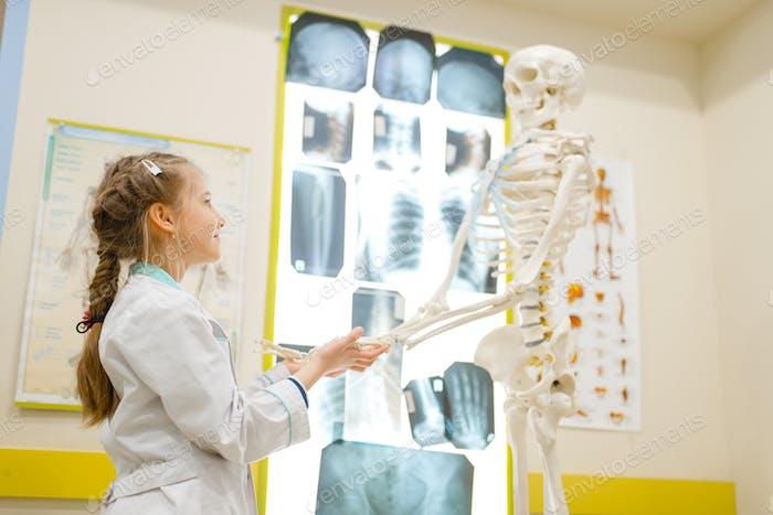 Girl in uniform playing doctor with human skeleton