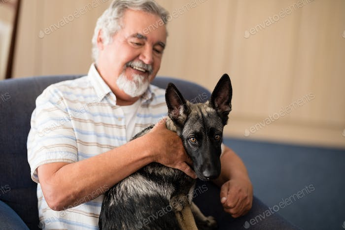 Happy senior man stroking puppy while sitting on armchair