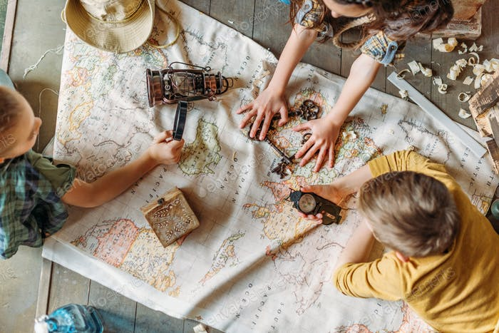 Overhead view of little kids travelers sitting together on porch with map