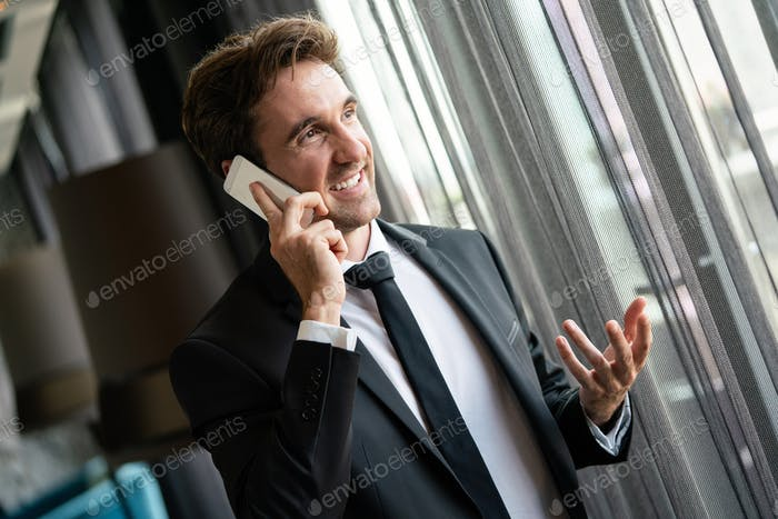 Successful happy businessman using mobile phone in office