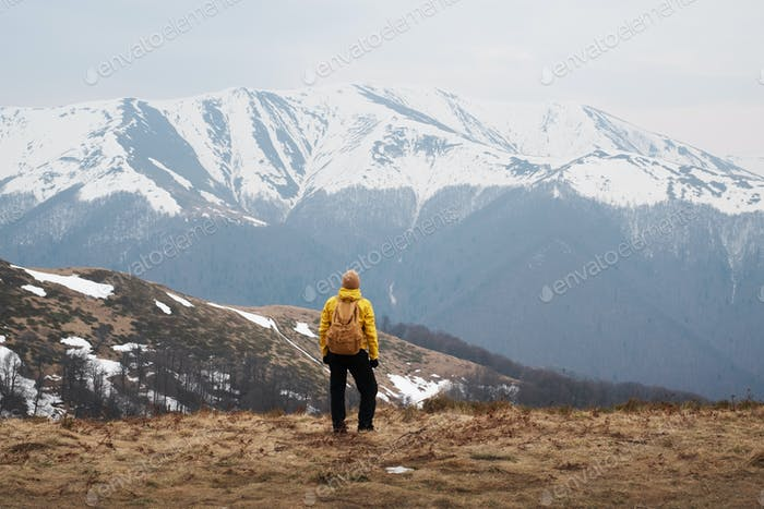 Man with backpack in spring snowy mountains