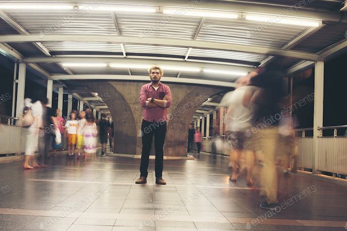 Hipster bearded man standing on the floor with people motion background while traveling at night.