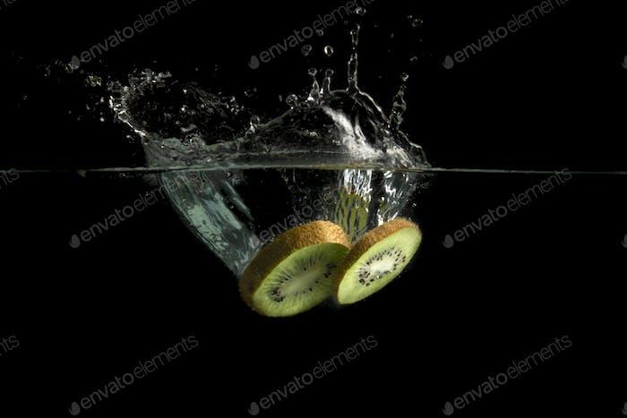 Kiwi fruit splashes in water