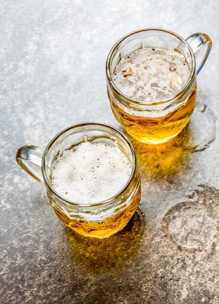 Two mugs of beer on stone background. Close up.