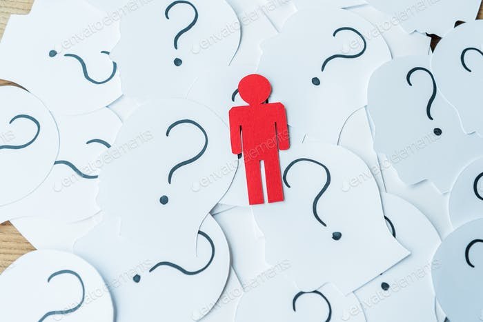 red human shape near question marks on paper with human heads on wooden table