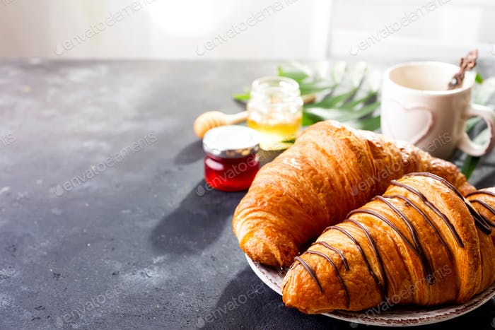 Breakfast on white wooden background - croissant, jam, berries and coffee, copy space