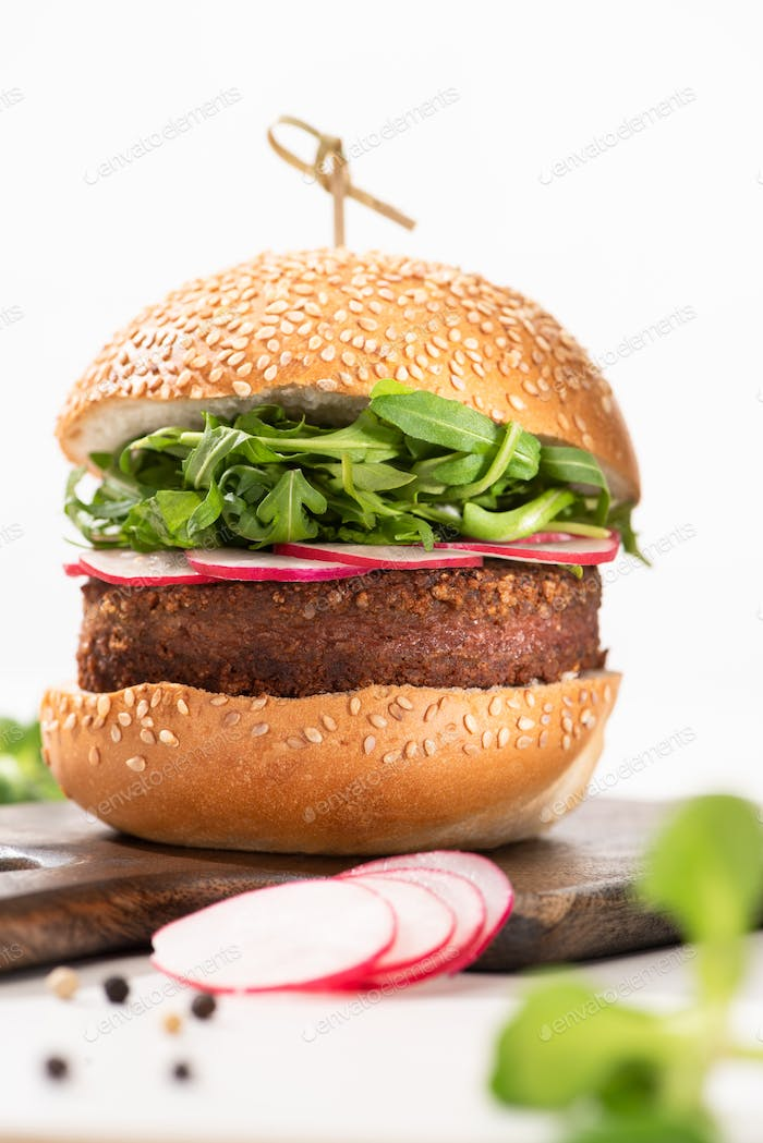 selective focus of delicious vegan burger with radish and arugula