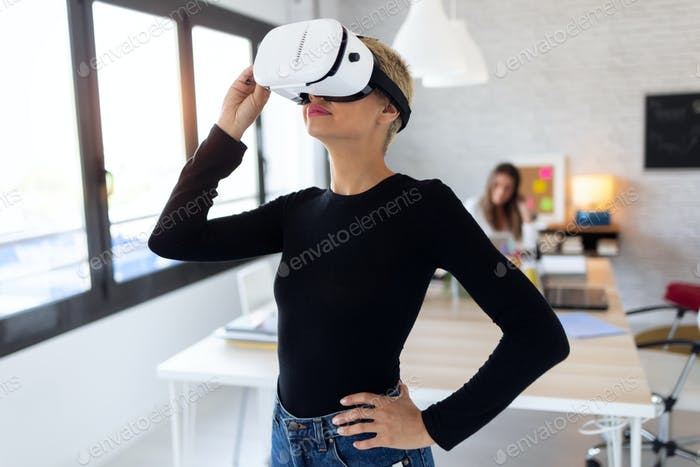 Modern young entrepreneur woman using virtual reality headset and enjoying the moment in the office.