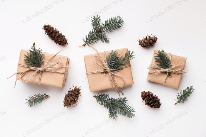 Christmas gifts, fir brancses and pine cones on white