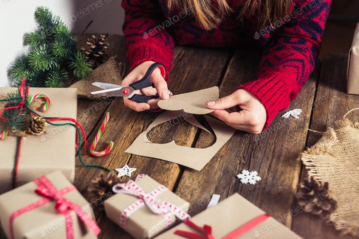 Male hands wrapping xmas gifts into paper and tying them up with