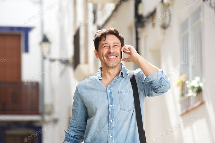 cheerful older man walking outdoors and making a phone call