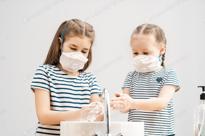 Girls are wearing face masks and washing their hands.