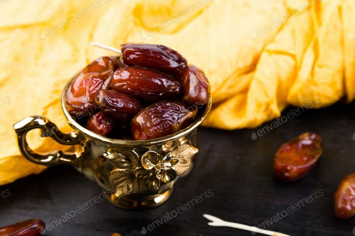 Dry fruit dates in golden cup near slate black heart. Copy space.