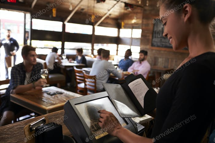 Young woman preparing bill at restaurant using touch screen